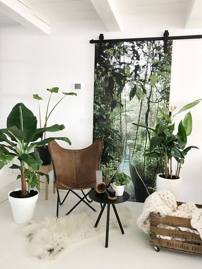 seating corner idea leather lounge chair with crossed hairpin legs small coffee table with round top and tripod legs ornate crate with crochet throw white shag rug potted greenery floral themed backdrop