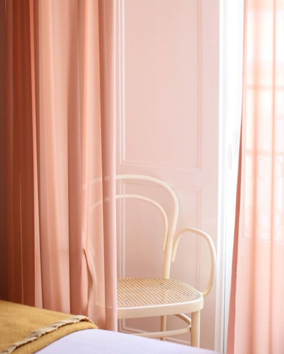 semi transparent curtains in pink soft neutral wicker chair white bed linen rust blanket