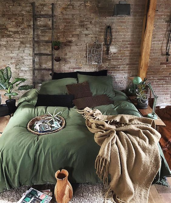 shabby brick walls with ornate leaning metal ladder for plants green duvet cover earthy brown throw blanket