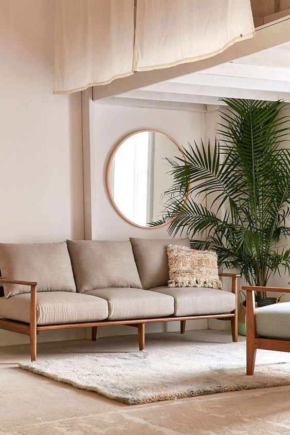 soft neutral living room clean lined and modern sofa with solid wood frame and removable cushion throw pillow white area rug round wood framed wall mirro