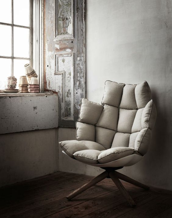 stylish lounge chair in white supported with tripod leg cushy and foamy upholstery
