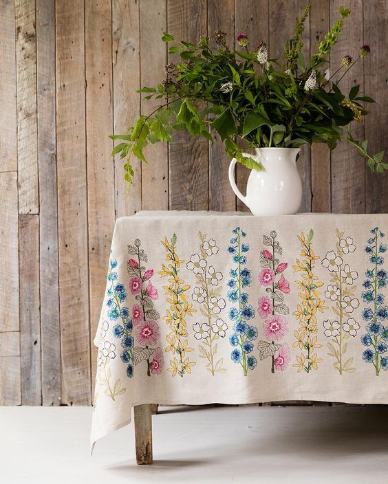 tablecloth with colorful flower patterns white porselain pot with vivid greenery wooden plank walls