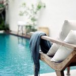 Teak Lounge Chair With White Throw Pillows And Blue Throw Blanket