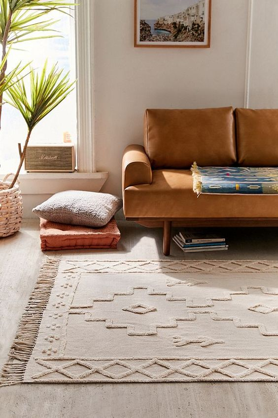 tufted area rug in soft neutral with geometric embroidery patterns and fringed trims along both edges earthy brown sofa