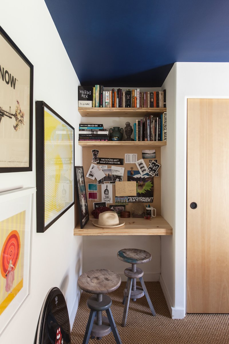 very tiny home office consisting of wooden book shelves floating wood desk vintage stools