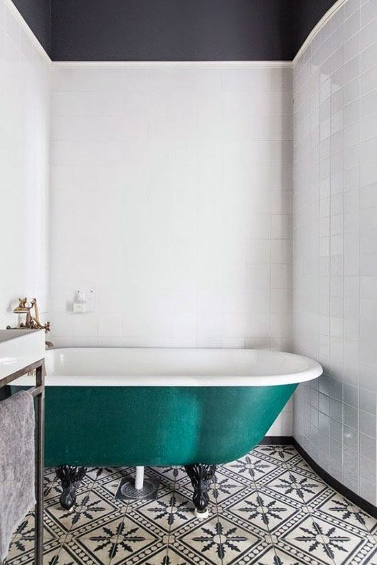 vintage claw foot bathtub in Marrs Green monochromatic geo patterned tile floors white ceramic tile walls