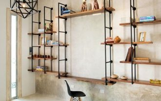warm industrial workspace black piping shelves with wood panels minimal wood working desk Scandinavian working chair cream concrete walls and floors herringbone patterned area rug in monochrome
