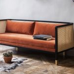 Wicker Sofa With Orange Cushion Gray Shag Rug Potted Suculent