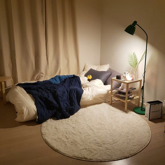 Korean style bedroom makeover idea floor mattress with white linen and navy blue duvet cover round shaped rug in white cream curtains simple wood bedside table