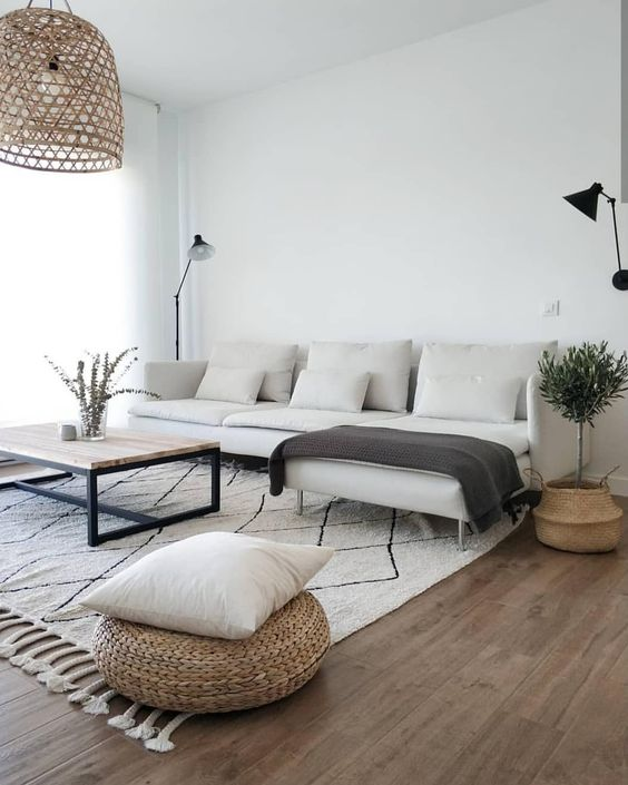 Scandinavian living room modern white sofa with additional chaise white area rug with black line accents and fringed trims wicker pouf pendant with oversized wicker lampshade