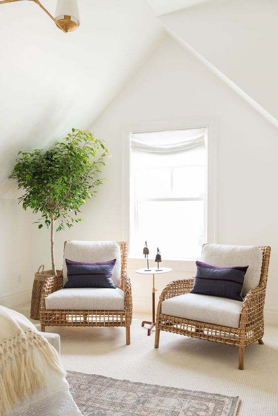 a couple of rattan chairs with white cushion addition and navy throw pillows vivid houseplant in the corner glass window
