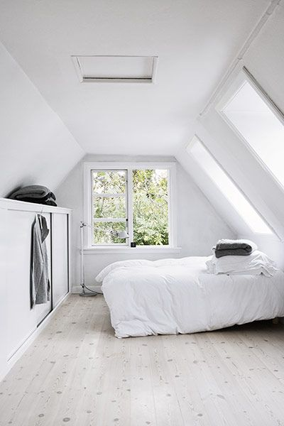 all white attic bedroom with walk in closet