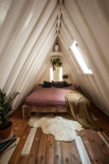 attic bedroom design fully exposed wood beams wood bed frame purple bedding linen brown throw blanket white shag rug wood plank floors
