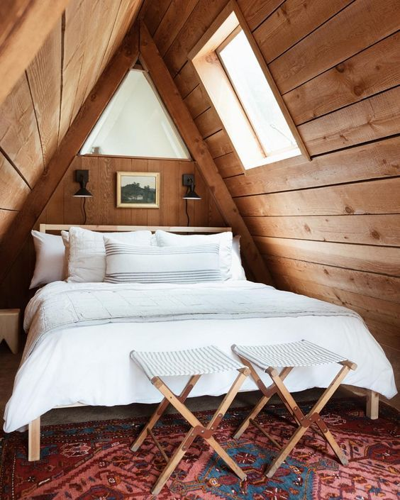 attic bedroom design wood plank ceilings with skylight white bedding treatment a couple of x base benchs vintage rug in brown