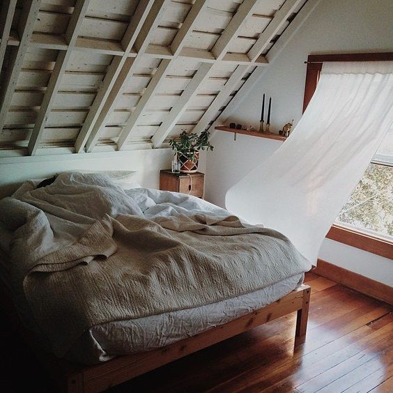 attic bedroom exposed wood beams in white wood bed frame off white bed linen and blanket glass window with wood trim white curtains