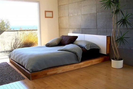 bare concrete tiled walls wood floors gray mat black bed linen soft blue duvet cover floor wooden bed frame with headboard potted houseplant