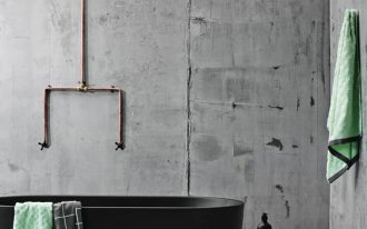bare concrete walls copper plumbing black bathtub wooden stool