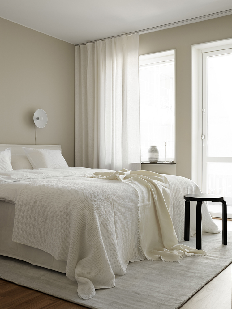 beige walls off white bed linen wood floors black stool white curtains