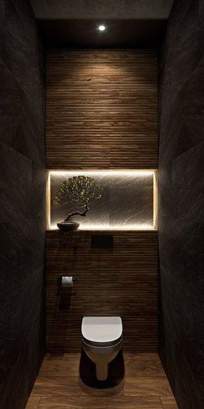 black concrete walls textured back wall with centered mini garden filled with bonsai and lighted frame