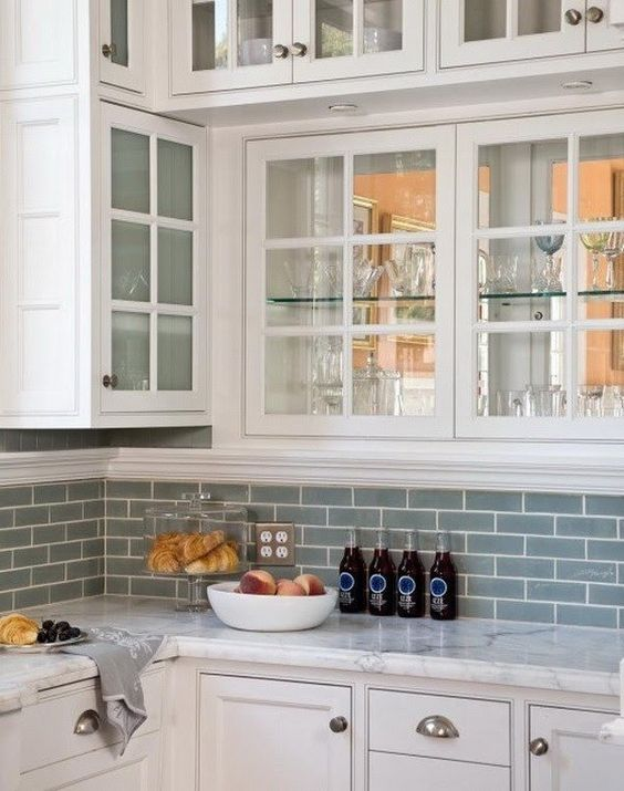 blue gray subway tiled backsplash with white grouts marble countertop white cabinets white trimed upper cabinets with glass door