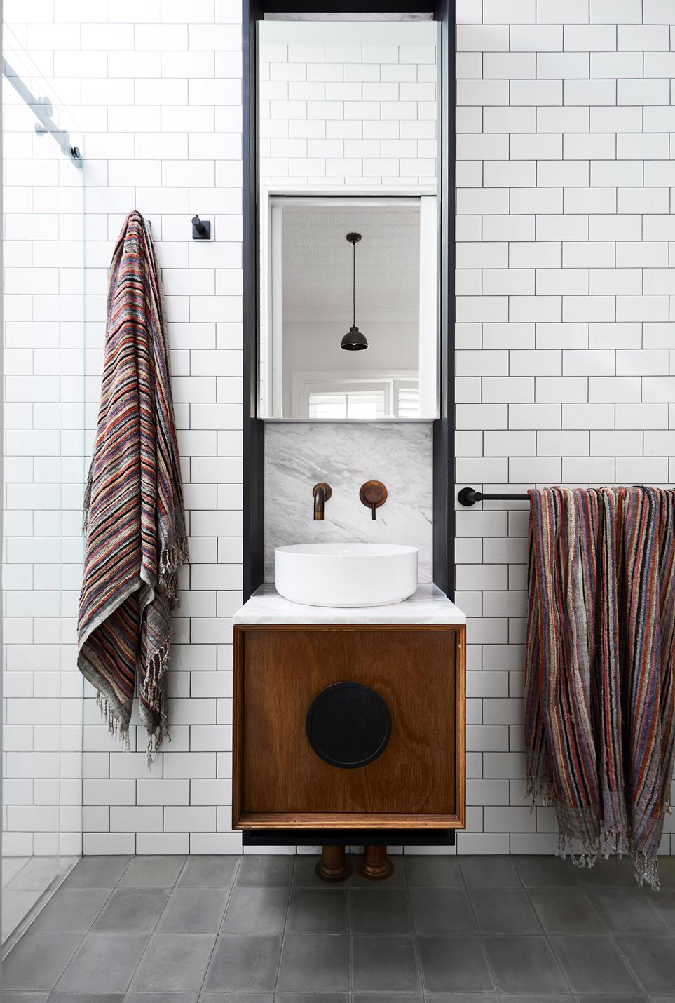 brick like subway tile walls narrow bathroom vanity with marble backsplash sink and wall mirror