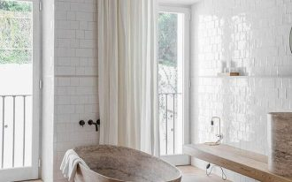 clean and warm bathroom soft toned bathtub light wood plank floors floating wood bench gloss subway tile walls in white off white draperies