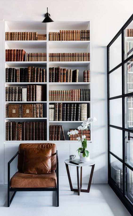 contemporary reading nook with industrial touch leather chair with metal frame recessed bookshelves in white with uncluttered books