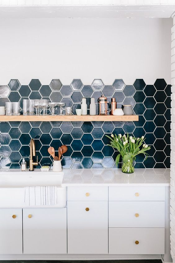 deep blue hexagon tiled backsplash organic wood shelf pure white kitchen cabinets and countertop potted greenery