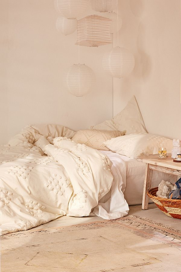different size paper lantern pendants floor bed with Boho duvet cover worn out area rug with tassels wood bedside table