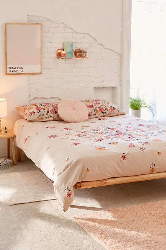 duvet cover with blooming floral patterns low profile bed frame white walls with white finish brick accent