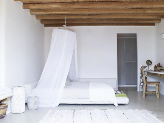 exposed wood beams bed with round shaped canopy with white canopy drapery white area rug white bedside tables