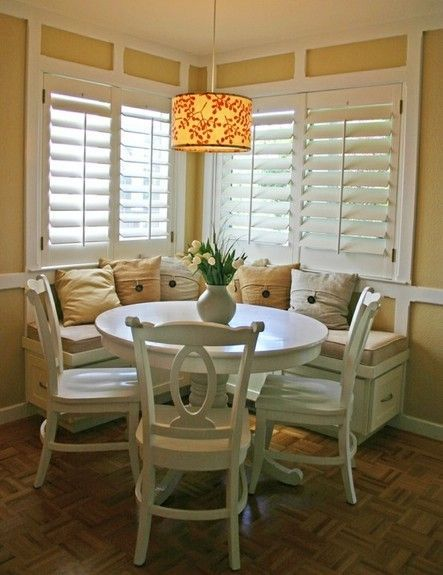 farmhouse style breakfast nook round top dining table in white traditional look dining chairs in white corner built in bench seat with under storage and throw pillows