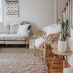 Flat Woven Area Rug With Fringe Tassels Rattan Chair With White Shag Throw Blanket Round Top Wood Side Table Midcentury Modern Sofa In Off White Boho Wall Decor