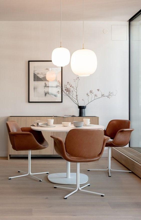 formal dining room leather dining chairs round top dining table in white pendant lanterns with warm light effect light wood floors