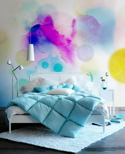fun and cheerful watercolor wall mural in pop of colors white bed frame with headboard in white white area rug white bed linen blue duvet cover