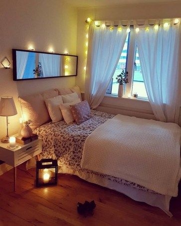 glass window with white curtains and string lamp accent floral bed line  white blanket white bedside table wood floors
