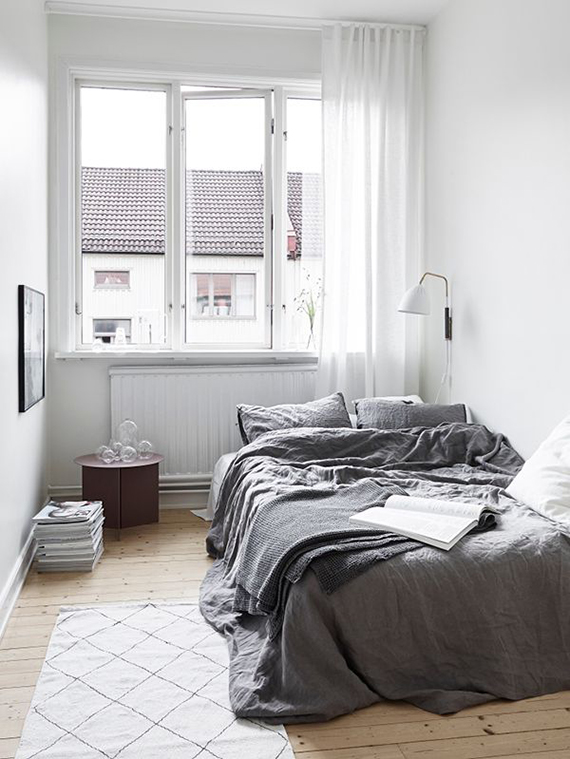 gray bedding treatment vintage area rug light wood floors glass windows with white curtains