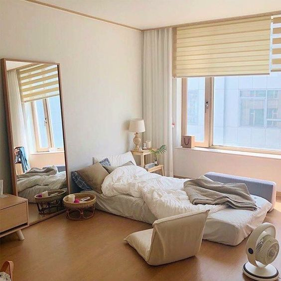 korean style bedroom floor bed with white bedding linen and duvet cover wood floors mirror leaning on the wall floor seat midcentury modern wood side table