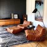 Leather Lounge Chairs Leather Foot Rest Modern Gray Area Rug With White Line Accents Wood Floors Modern Floor Lamp Black Wall Wood Hall Console Table