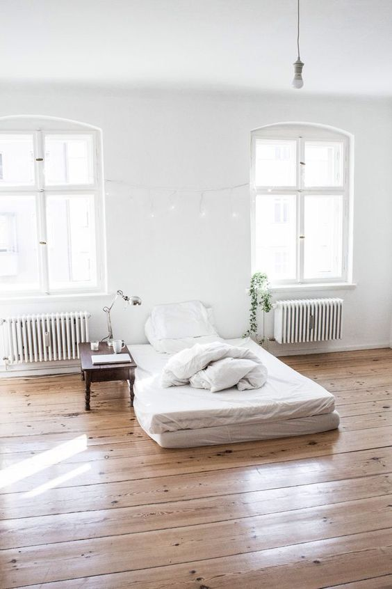 light and bright bedroom design floor mattress with white bedding treatment dark wood side table wood plank floors a couple of glass windows with trims
