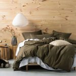 Light Wood Wall Panel White Bed Linen Deep Olive Green Duvet Cover And Pillows Tree Trunk Side Tables Modern Pendant Lantern In White