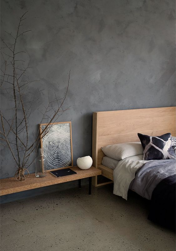 matte black walls concrete floors midcentury modern bed frame with wood headboard wood bench seat in industrial style ornate dried houseplant