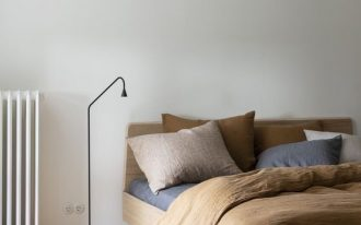 midcentury modern bed frame with headboard tiny floor lamp in black milo colored duvet cover blue bed linen