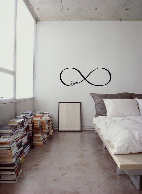 minimalist bedroom design platform bed white comforter bare concrete ceilings white walls piles of books