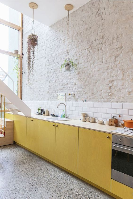 minimalist kitchen sunny yellow cabinets hard textured brick walls in whitewashed finish white subway ceramic tile backsplash