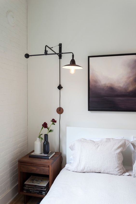 minimalist white bed with white headboard contemporary wooden bedside table contemporary light fixture black framed painting
