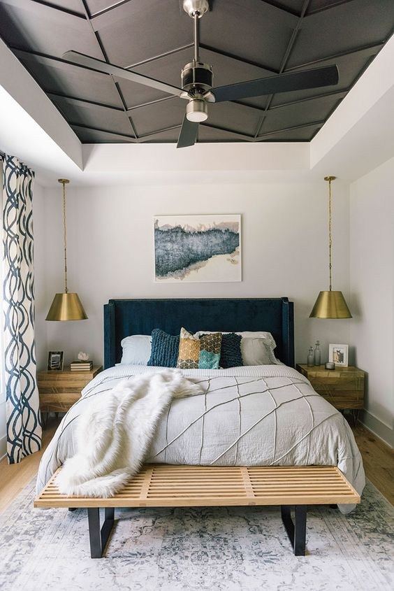 modern bed frame with navy blue headboard white bed linen and duvet cover fury throw blanket in white worn out area rug a pair of hanging night lamps with gold toned lampshade wooden be