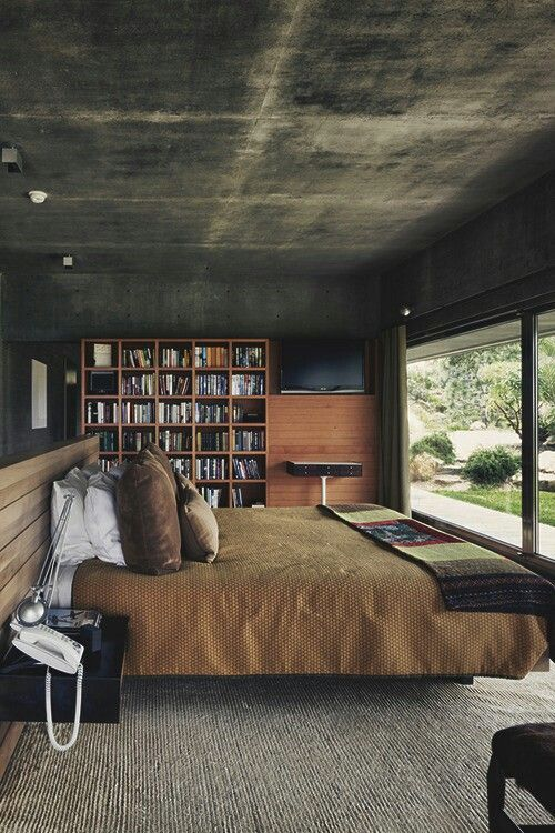 modern bedroom design with bare concrete ceilings and walls wood bookshelves modern bed with wood paneling headboard brown bedding linen huge glass window