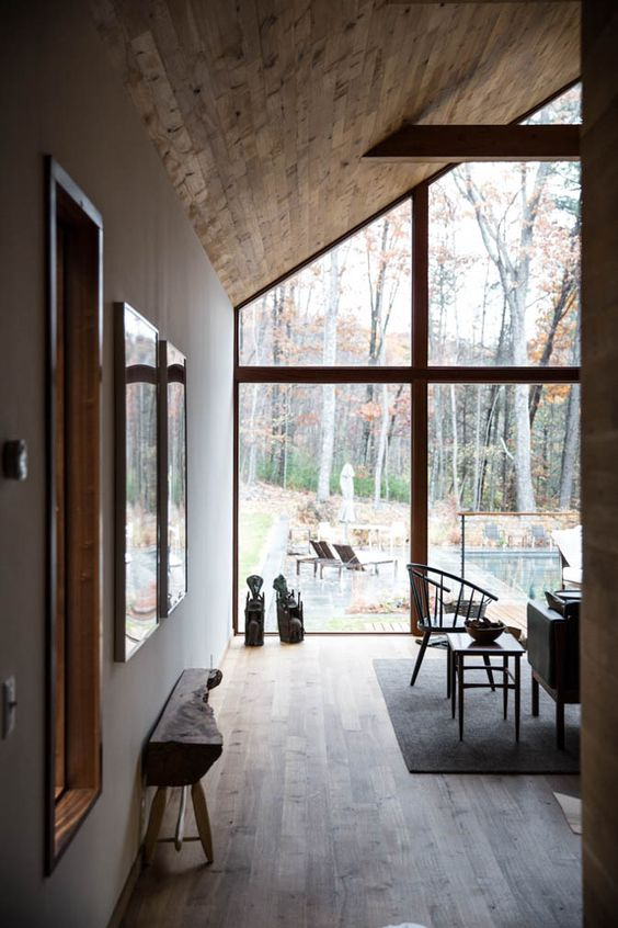 modern cabin's interior with fully glass windows with wood trims and slanted wood ceilings