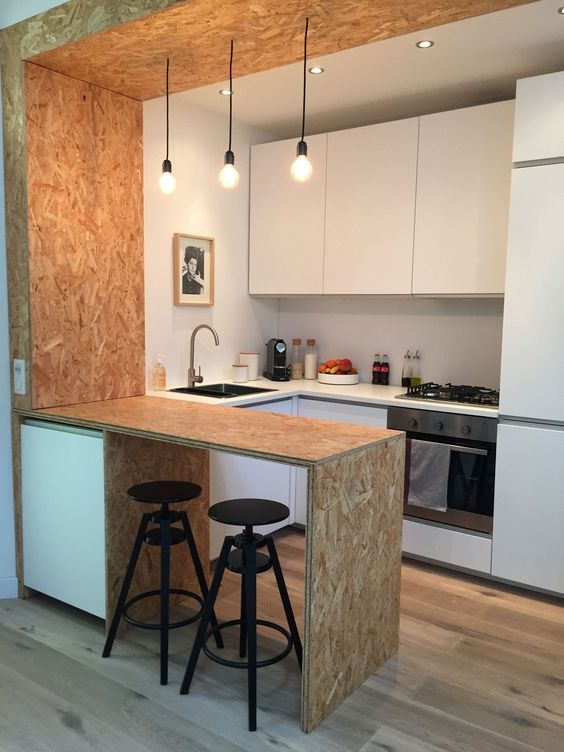 modern industrial kitchen and breakfast nook with wood veneer finish black wrought iron bar stools clean line kitchen cabinets stainless steel kitchen utensils industrial style pendants